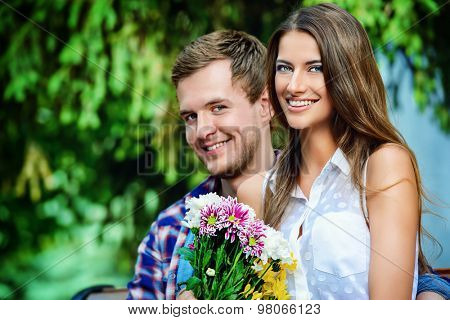 Young man giving flowers to his sweetheart girl. Sunny summer day.