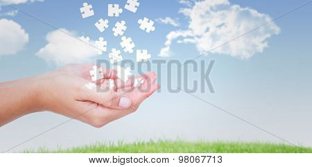 Hands presenting against blue sky over grass