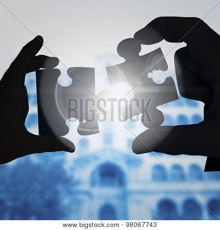 Mid section of a businessman in suit with hands out against jigsaw