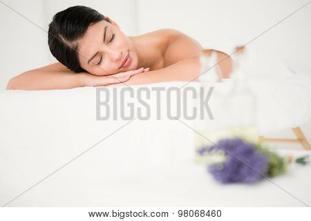 Beautiful woman lying on the massage table at the health spa