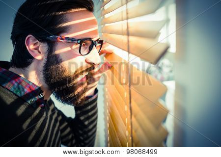 Hipster businessman peeking through blinds in his office