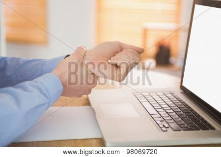 Businessman clutching his painful wrist in his office