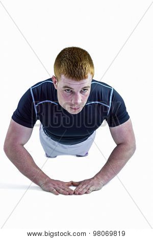 Muscular rugby player doing push ups on a white background