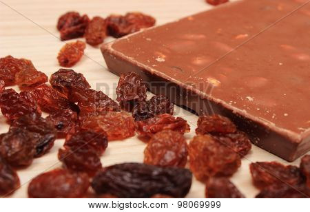 Nutritious Chocolate With Nuts And Raisins On Wooden Table
