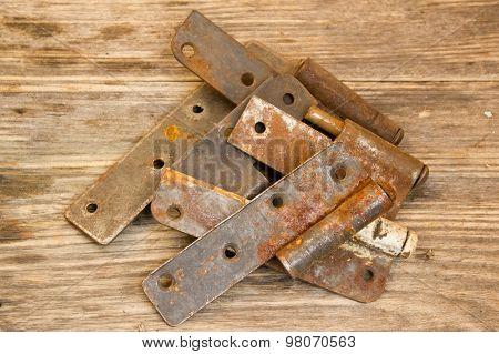 Metal Door Hinge On A Grungy Wooden Background