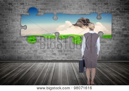 Back turned businesswoman holding a briefcase against field with rock and cloud