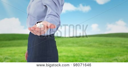 Businesswoman presenting with hand against blue sky over green field