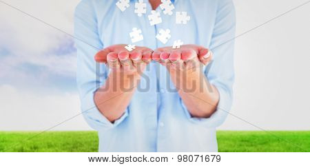 Womans hands presenting against blue sky over green field