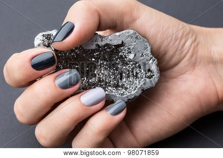 Female hand with textured silver mineral