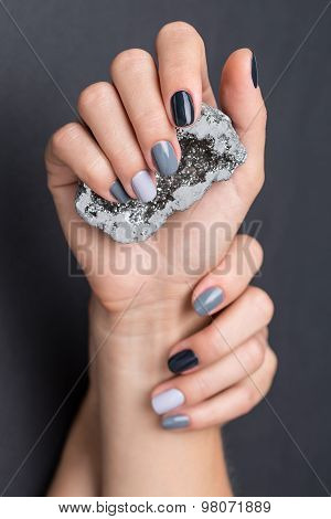 Female hands with textured silver mineral