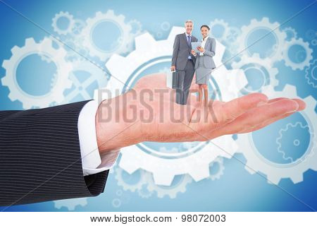 Business people using tablet computer against white wheels and cogs on blue