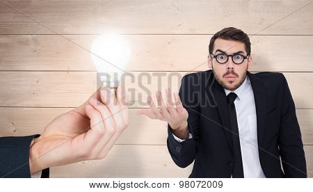 Doubtful businessman with glasses gesturing against overhead of wooden planks