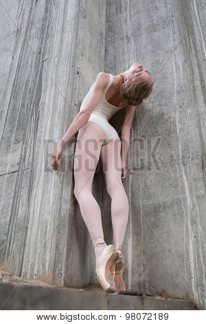 Slender ballerina on a background of the concrete