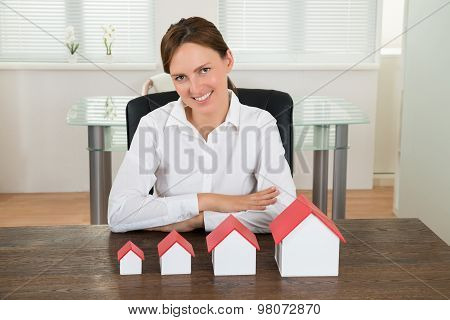 Businesswoman With House Models At Desk