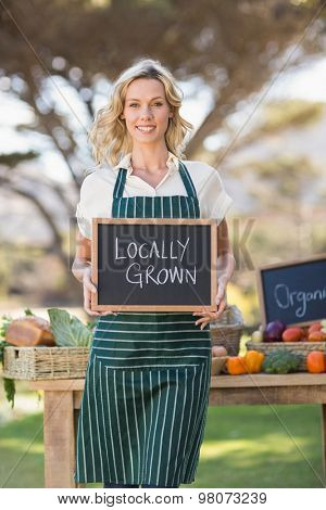 Portrait of a farmer woman holding a locally grown sign