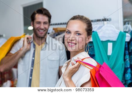 Portrait of smiling woman with shopping bags standing in front of her man in clothing store