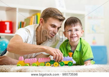 Family time. Kid boy joyfully playing building blocks with his father