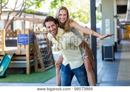 Portrait of smiling woman piggy-backing on her boyfriend at shopping mall
