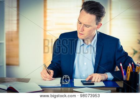 Concentrated businessman writing down in his office