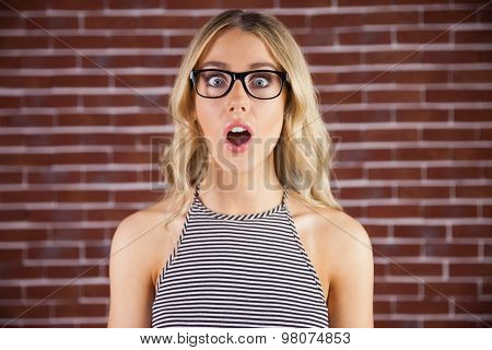 Portrait of gorgeous blonde hipster being shocked against red brick background