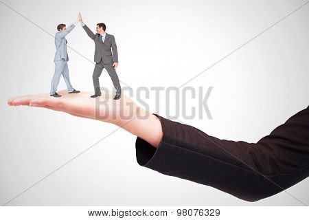 Businessmen high fiving against white background with vignette
