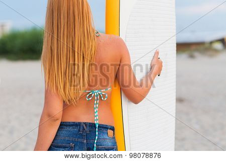 sea, summer vacation, water sport and people concept - woman with surfboard on beach from back