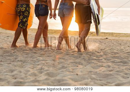 friendship, sea, summer vacation, water sport and people concept - close up of friends wearing swimwear with surfboards on evening beach from back