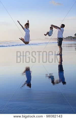 Positive Family Having Fun On Black Sand Sea Beach