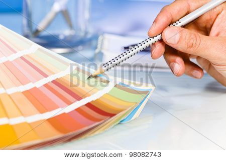 Artist Hand Pointing To Color Samples In Palette