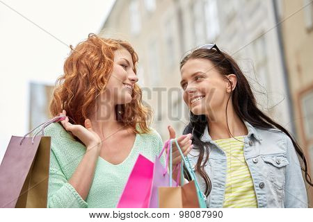 vacation, sale, leisure, consumerism and friendship concept - smiling happy young women or teenage girls with shopping bags on city street