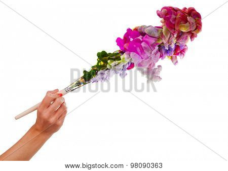 Woman hand holding brush with colored ink splashes. Isolated on white background