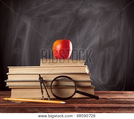 School books still life with accessories placed on wooden table. Black board on background