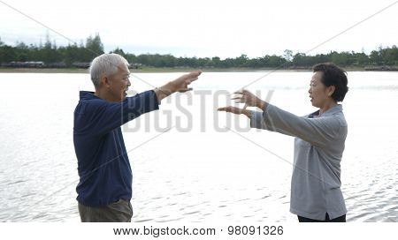 Asian Senior Elderly Couple Practice Taichi, Qi Gong Exercise Next To The Lake