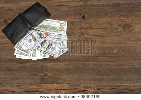 Men's Wallet With Dollar Cash On The Rough Wood Background