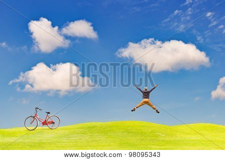 Happy Man Jumping On Green Grass Field