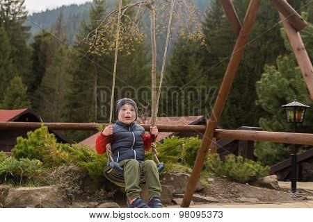 Boy swinging on a swing, boy smiling