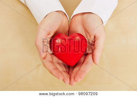 Woman holding red heart in her hands as symbol for love and care