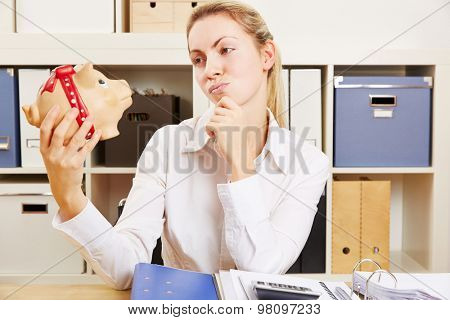 Pensive business woman lookinh at piggy bank and thinking about saving money