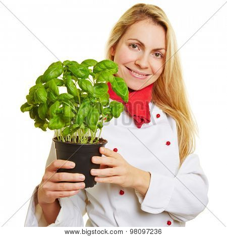 Happy young woman as chef cook with basil herbs in her hands