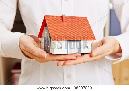 Hands of a woman holding house as concept for a building insurance