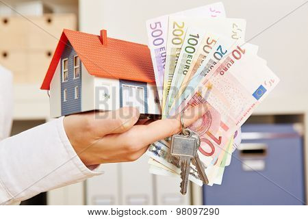 Hand of a woman with house and Euro money and door keys