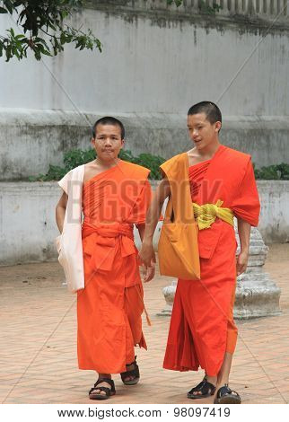 two buddist monks are walking on the street in Luang Prabang