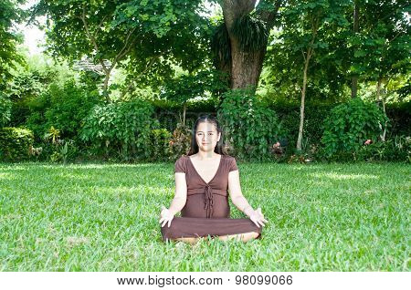 Pregnant woman sitting in the park