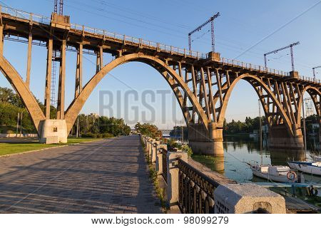 Walking Stone Embankment Along  Dnieper River And Old Openwork Bridge.