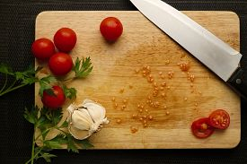 picture of black-cherry  - Preparation of cherry tomatoes garlic and parsley with chefs knife on wood cutting board on a black background - JPG