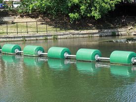 stock photo of safety barrier  - Safety barrier across a river to protect people in boats - JPG