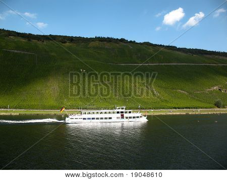 The white ferry under blue sky and shadows on the Mosel river.