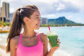 Sport fitness woman drinking healthy green detox juice, vegetable smoothie at running workout on bea poster