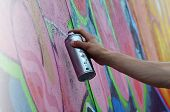 Постер, плакат: A Young Red haired Graffiti Artist Paints A New Graffiti On The Wall Photo Of The Process Of Drawin