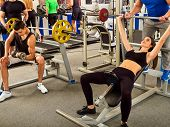 Fitness friends workout gym. Woman working on bench press. She lifting heavy barbell. Man backs girl poster